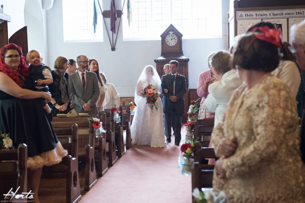 The father of the bride walks his daughter up the aisle