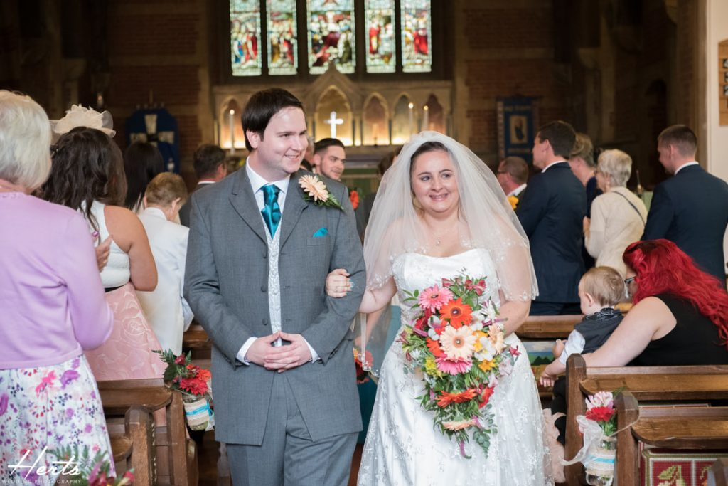 The couple smile as they leave the church