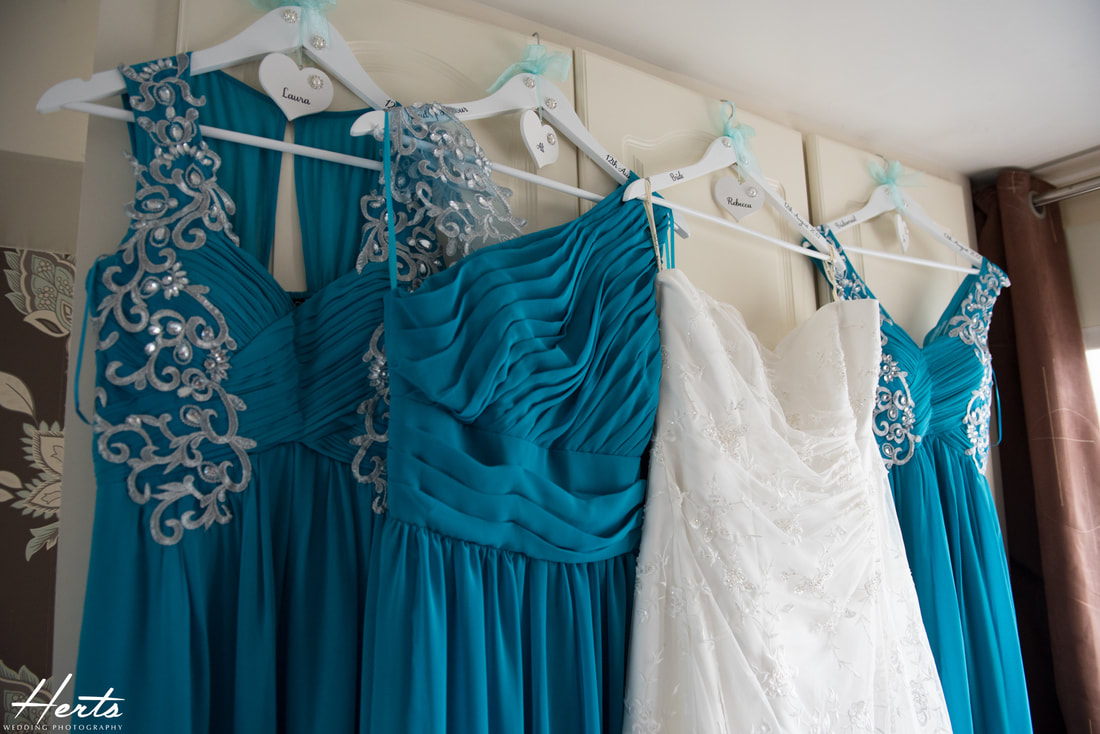 The wedding dresses hang next to each other