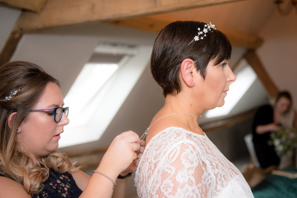The brides' daughter puts on the bride's necklace