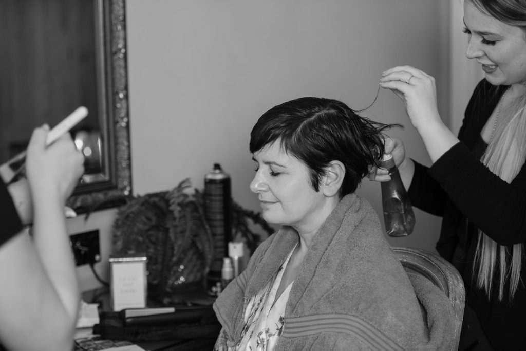 The bride having her hair styled by the redcoats wedding photographer, Steve
