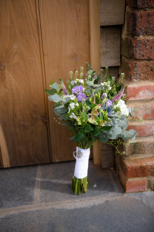 The wedding bouquet sits by a doorway
