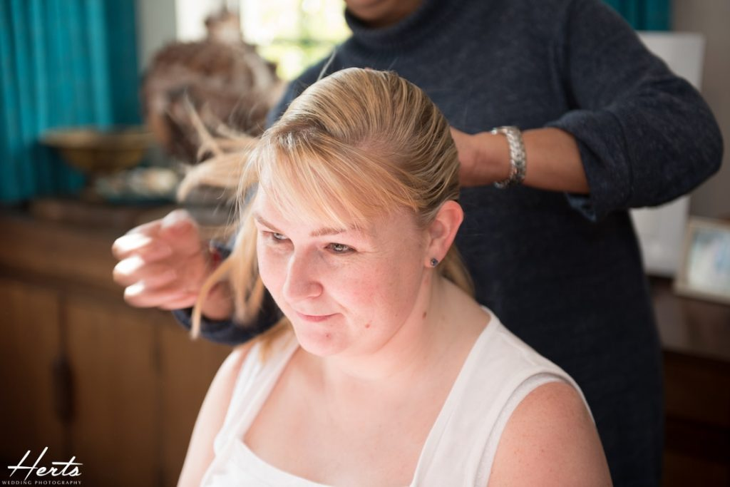 The sister of the bride has her hair styled