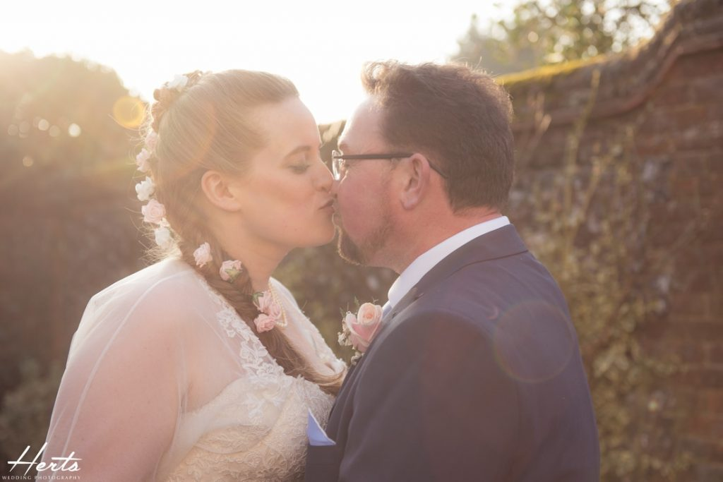 The happy couple share a kiss in the sunlight