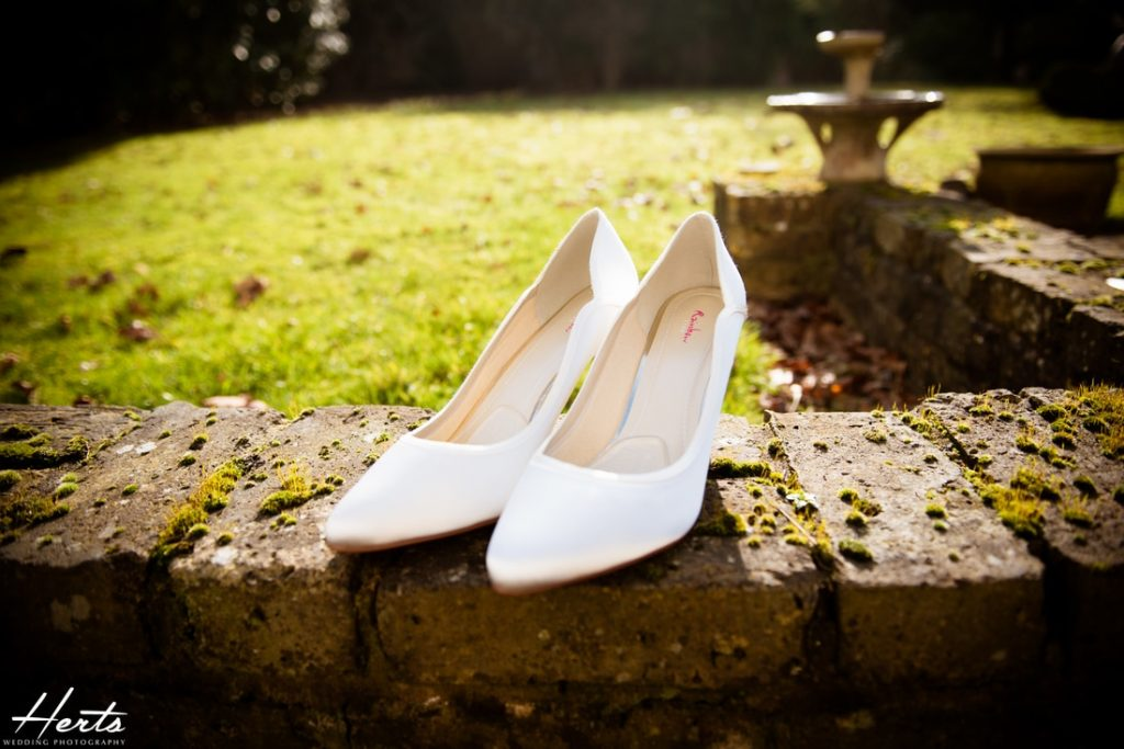 The bride's rainbow shoes on a brick wall