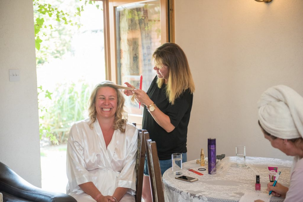 The bride having her hair styled