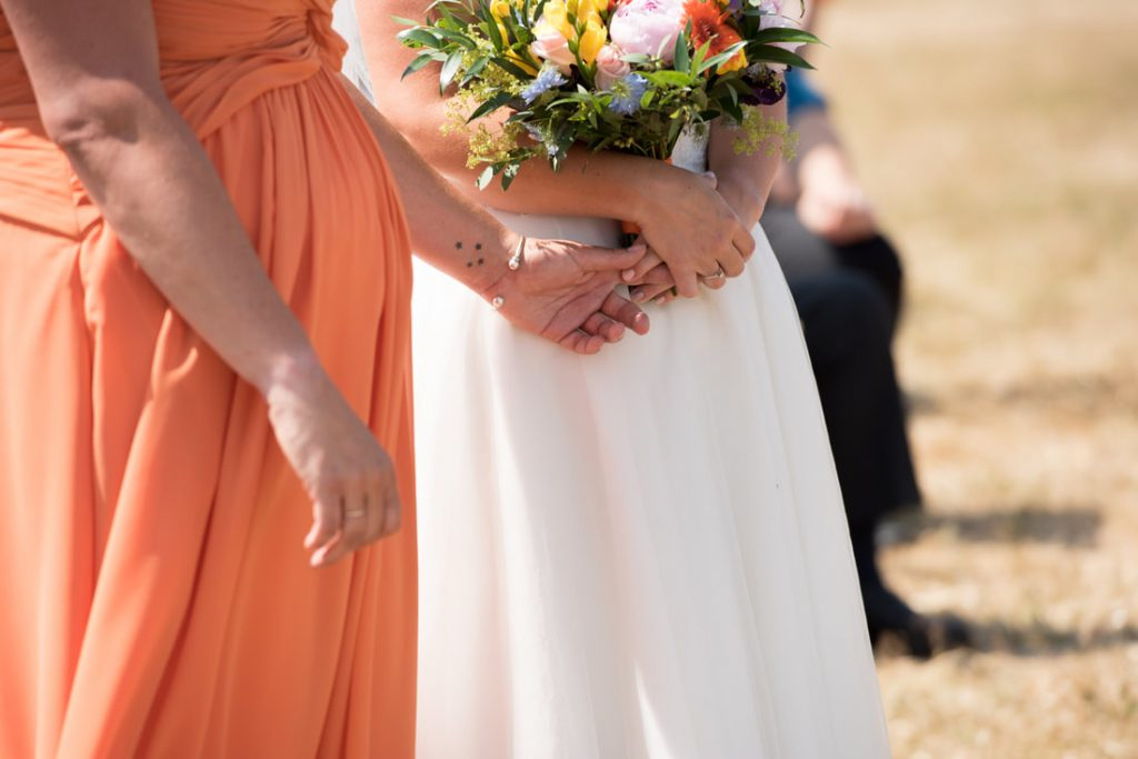 The two brides hold hands