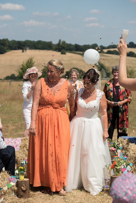 The two brides leave under a shower of confetti