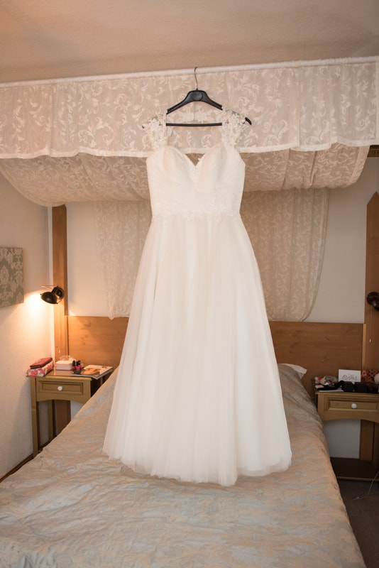 The wedding dress hangs from the bed
