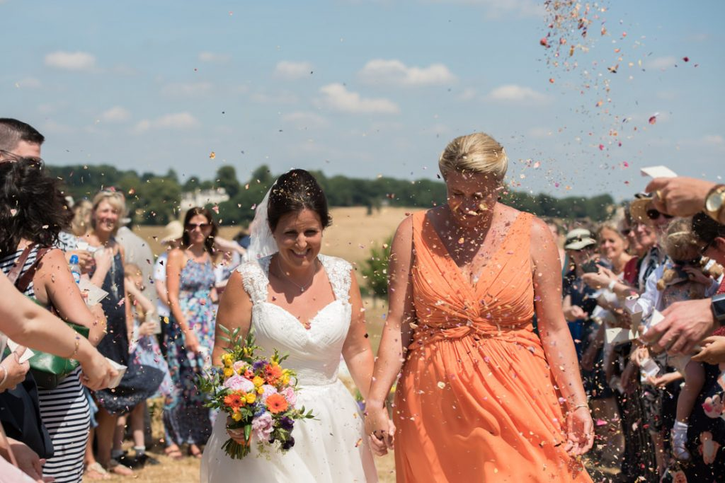 The two brides are showered in confetti