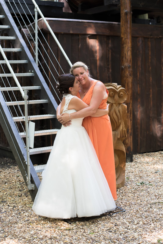 The two brides share an embrace