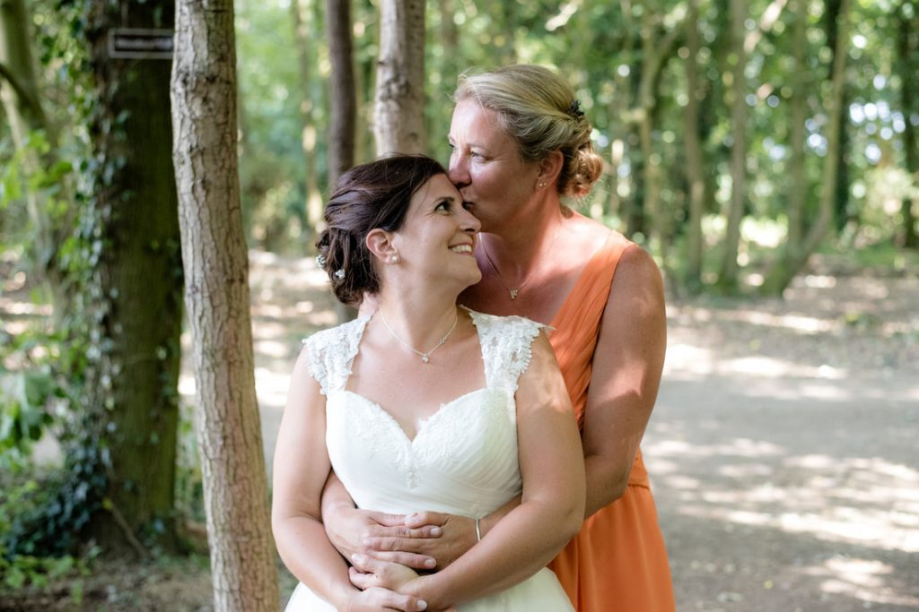 A bride kisses the other on the forehead
