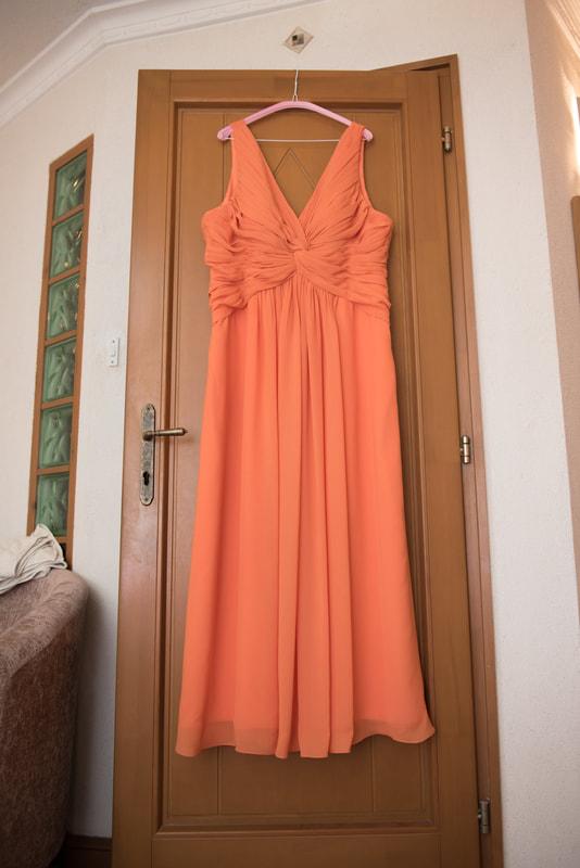 Orange wedding dressing hanging from a door