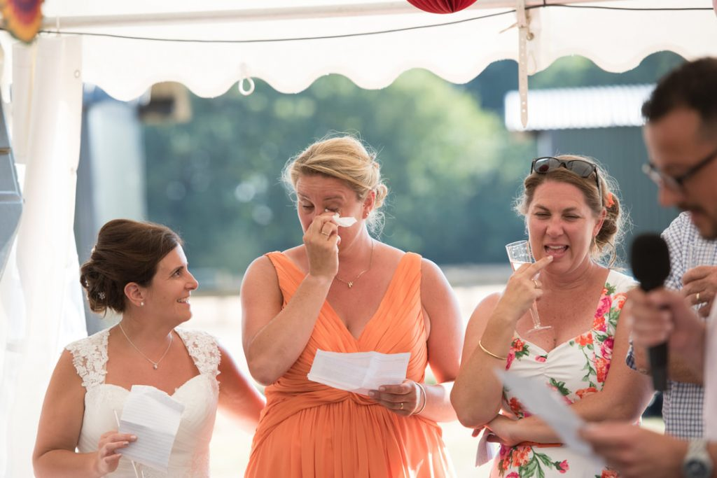 A bride wipes a tear away from her eye