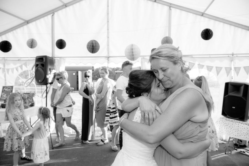 The two brides embrace