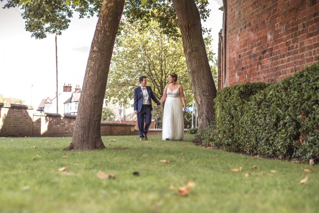 The brides walking between trees at st albans register office