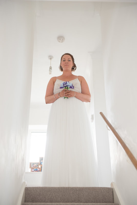 The bride standing at the top of the stairs