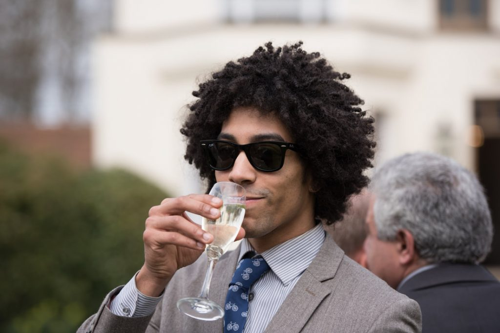 A wedding guest drinking champagne
