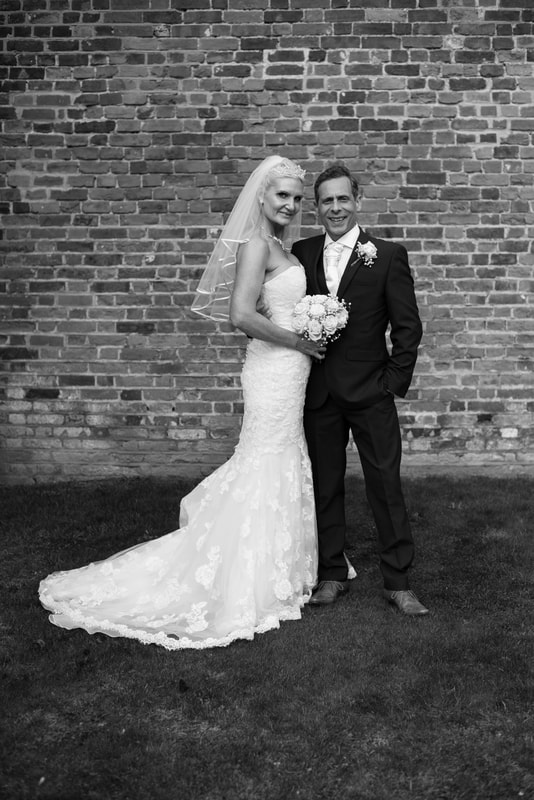 The bride and groom pose together with a brick wall in the background