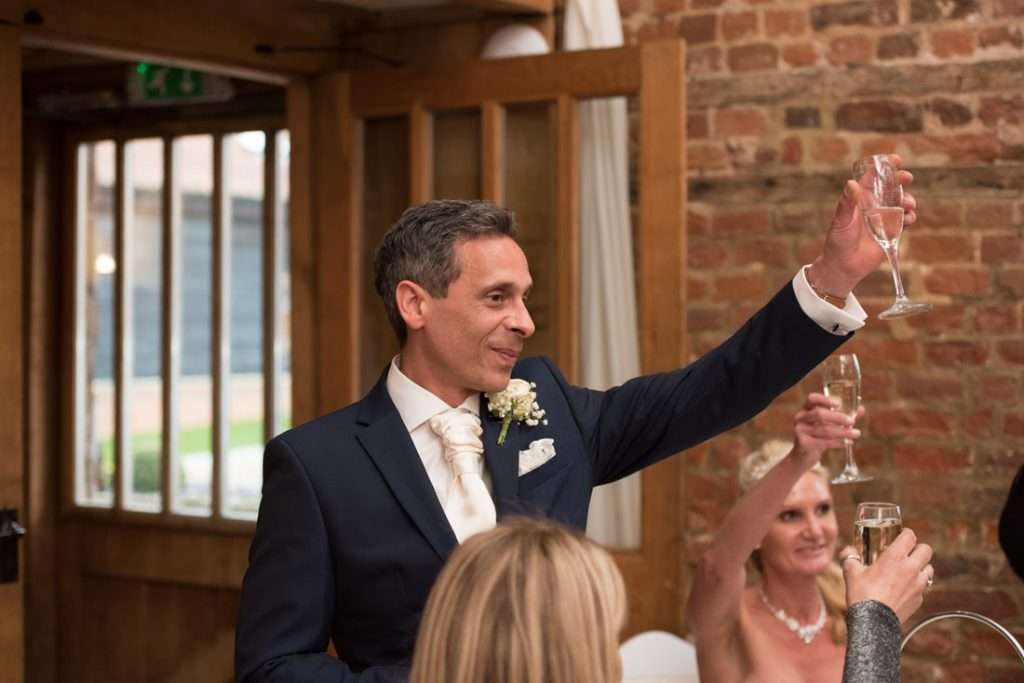 The groom raises his glass to propose a toast