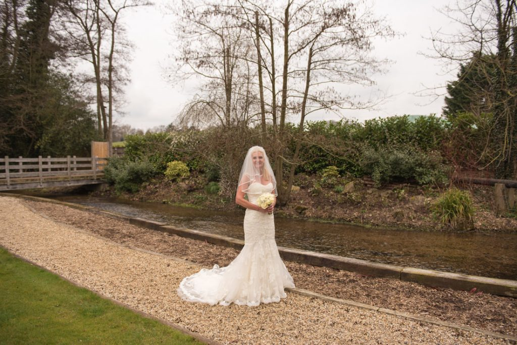 The bride standing besides a small stream