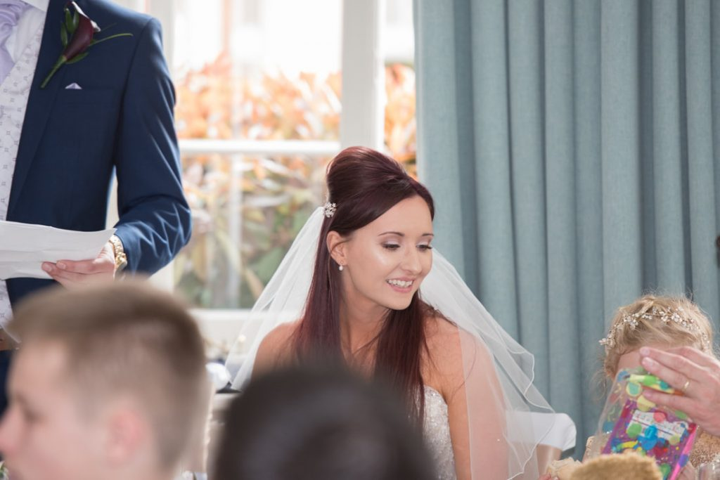 The bride sits and smiles at the top table