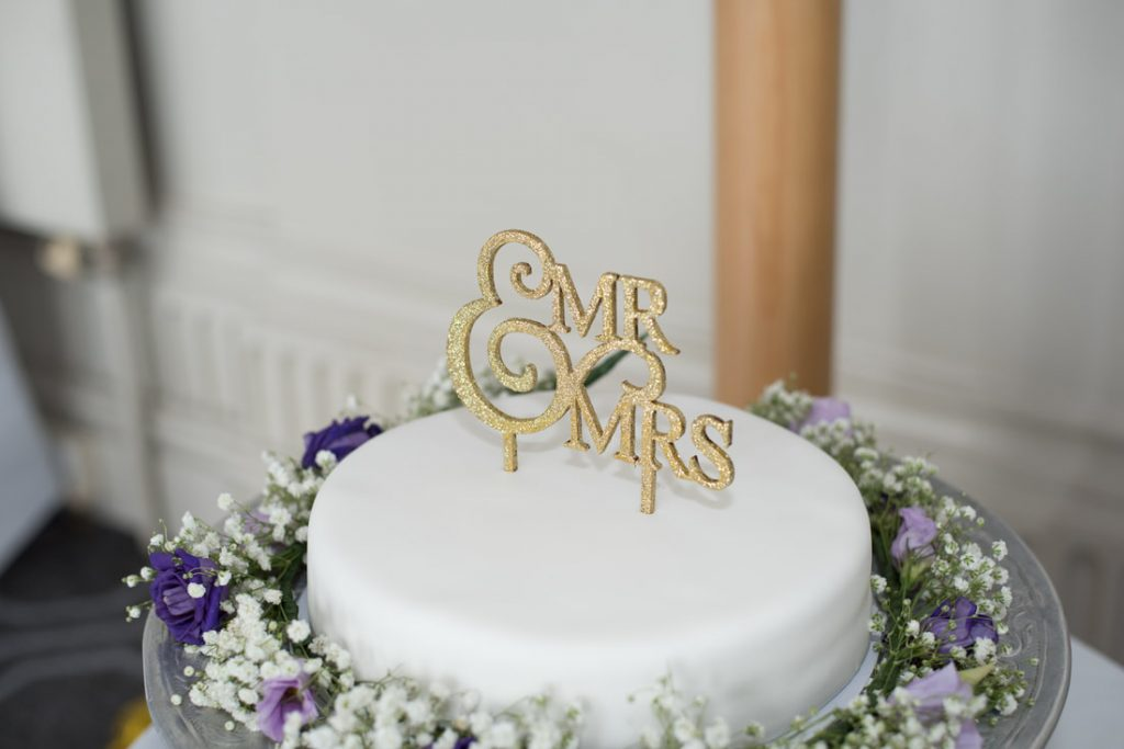 A wedding cake with a mr & mrs topper