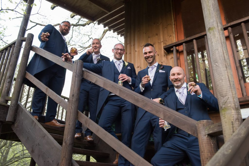 The groom and his groomsmen stand on the stairs