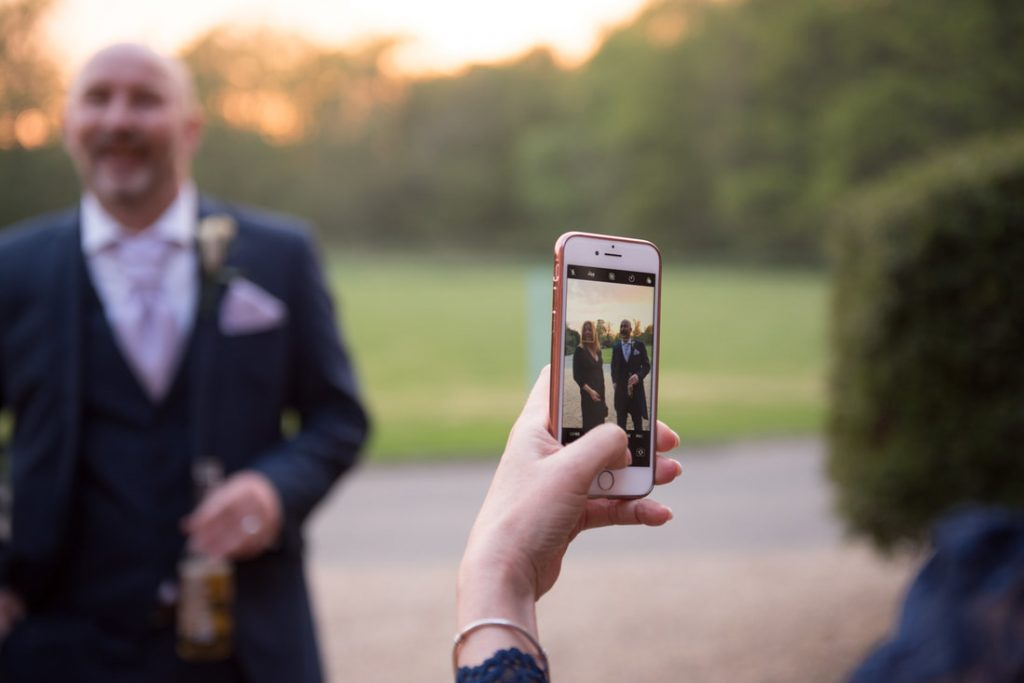 A guest takes a photo on his phone