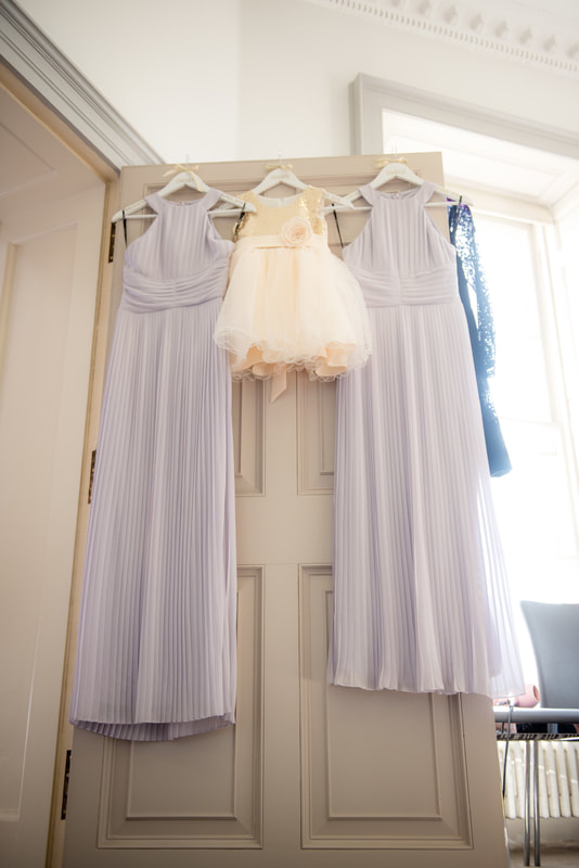 The bridesmaid dresses hang on a door