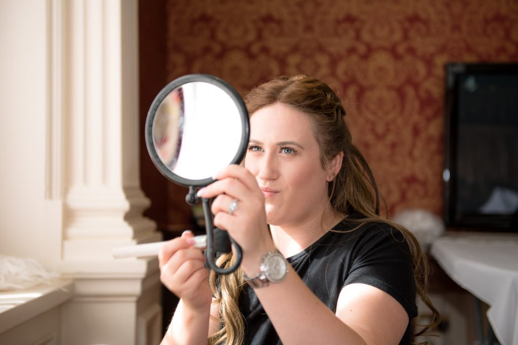 The bride checking her makeup in a handheld mirror
