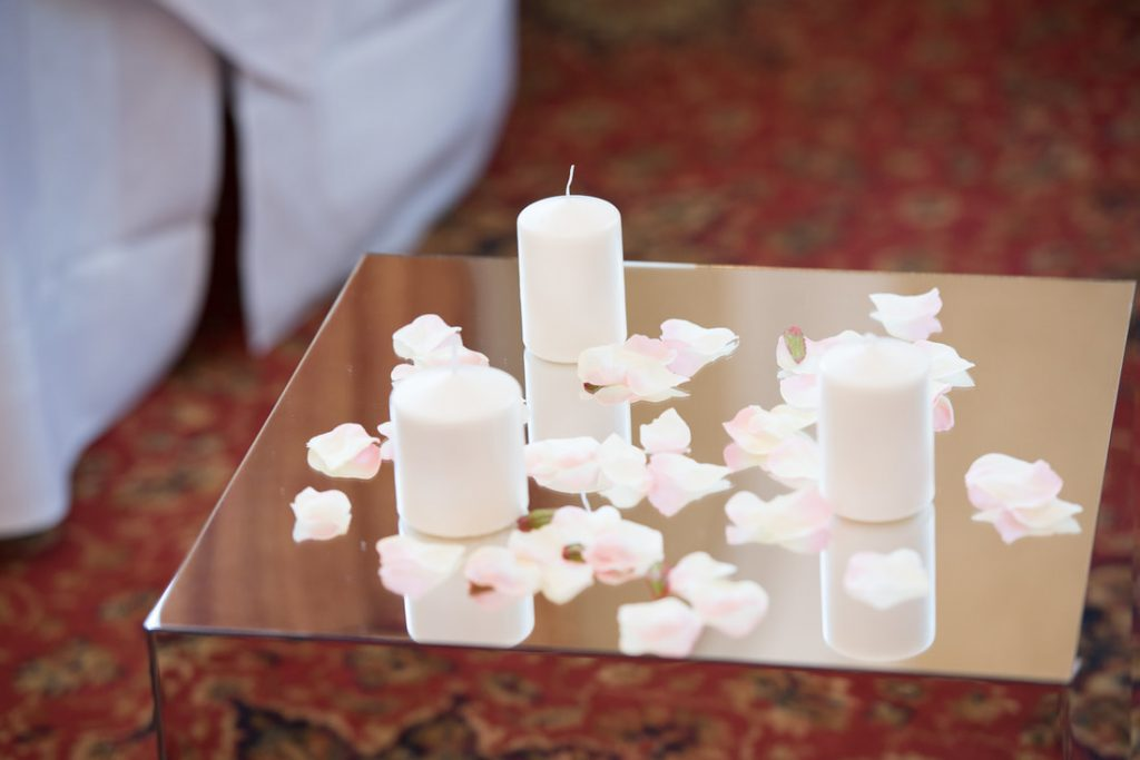 Candles and petals on a mirror table