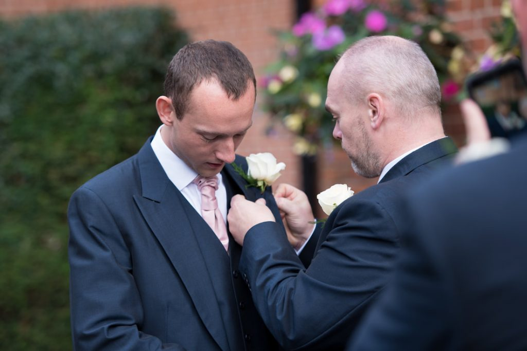 The best man adjusting a groomsman