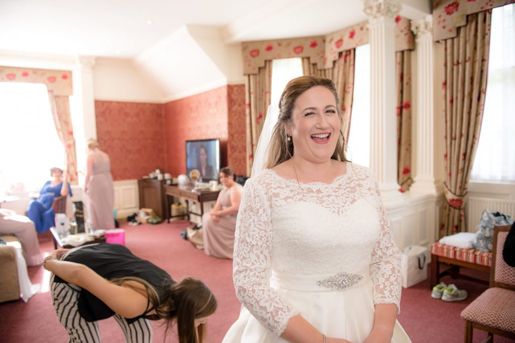 The photographer shares a joke with the bride