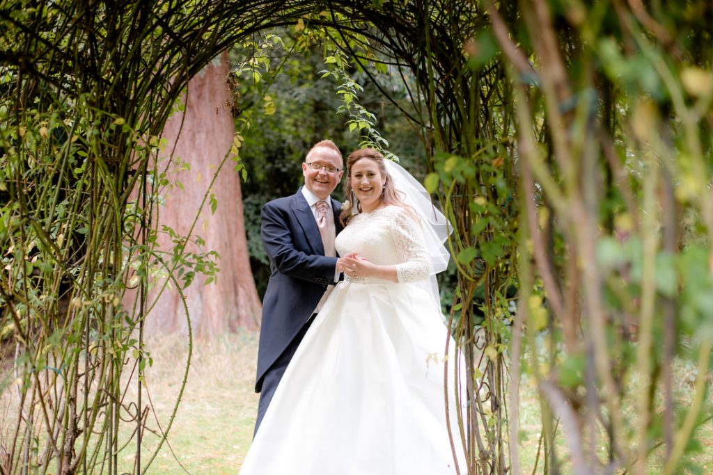 The bride and groom under an archway of trees