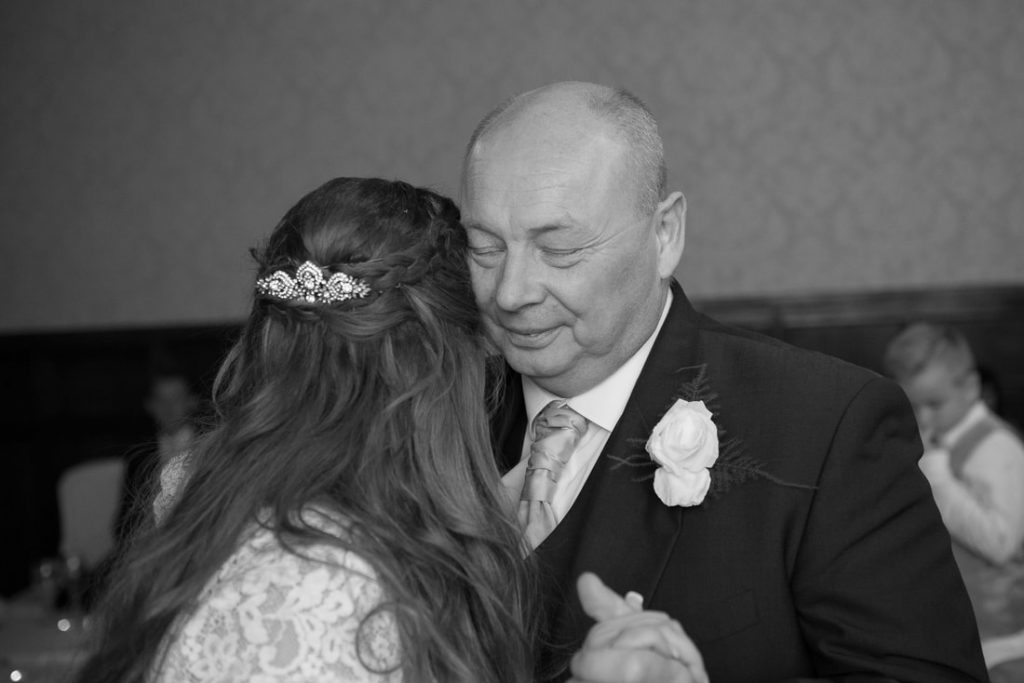 Father and daughter dance together at grims dyke hotel