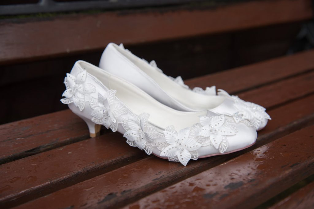 Lovely white wedding shoes on a wooden bench