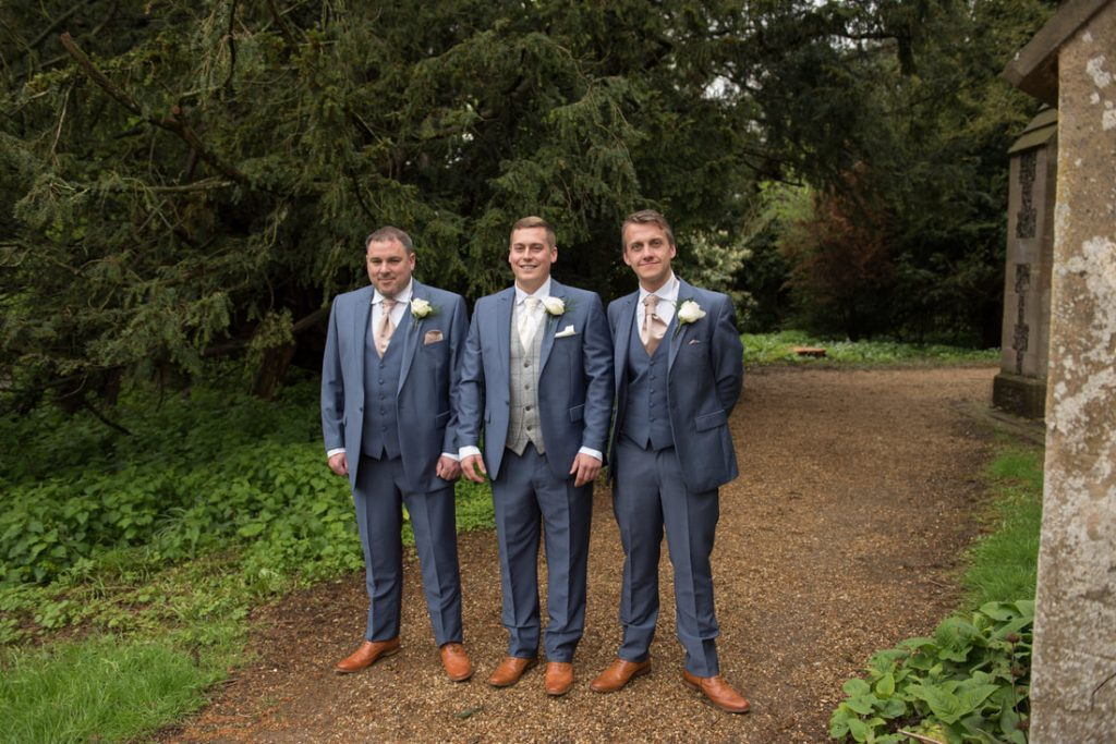 The groom and his groomsmen standing together outside the church