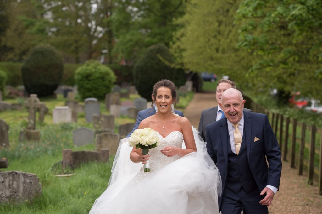 The bride and her father walking up to the church