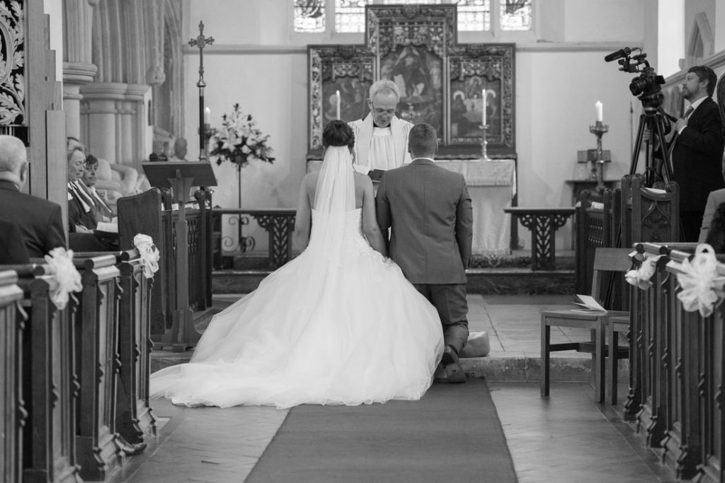 The bride and groom kneel to receive their marriage blessing