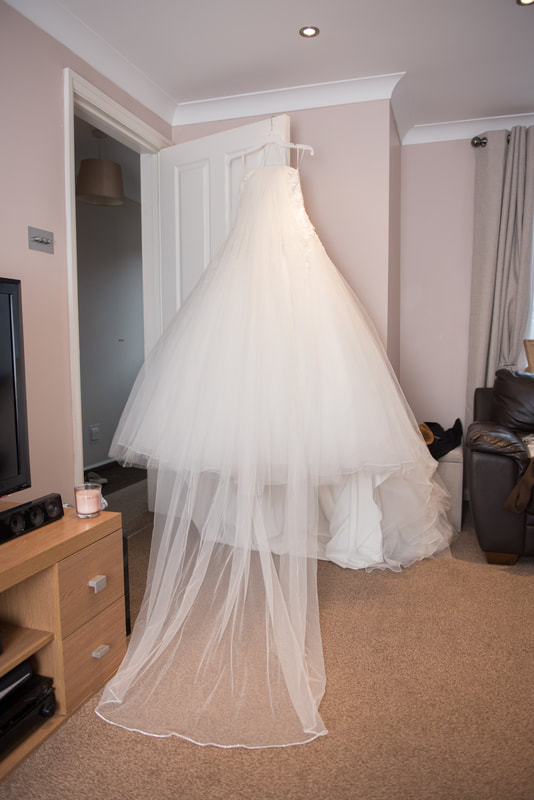 The wedding dress hanging from a door