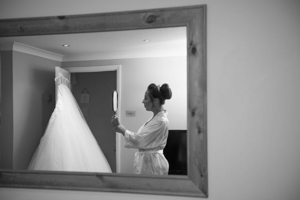 The bride looking in the mirror with her dress hanging in the background