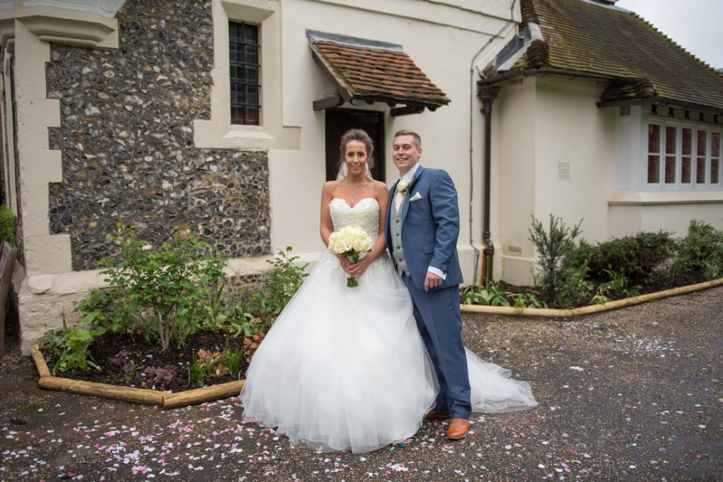 The bride and groom pose for photos outside of the Ware Priory