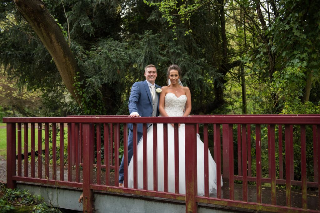 The bride and groom on the bridge outside ware priory