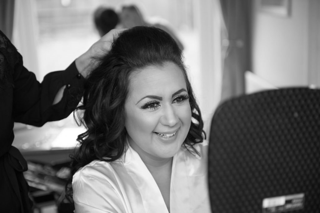 The sister of the bride having her wedding hair styled