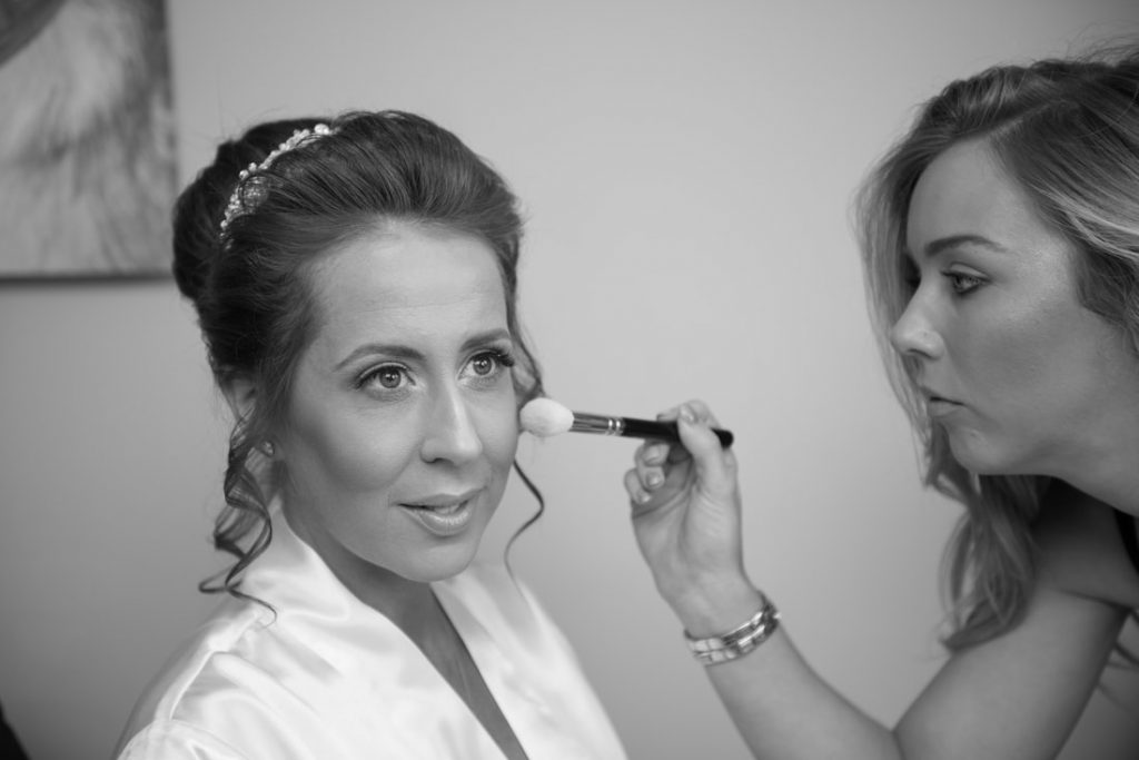 The bride having wedding makeup applied