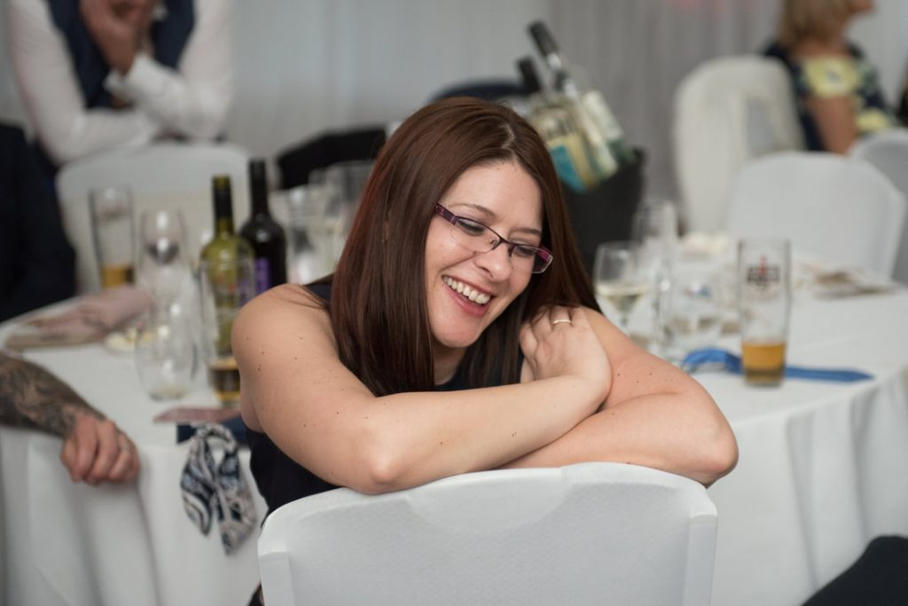 A smiling wedding guest seated backwards on a white chair