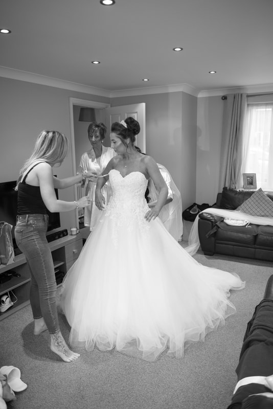 The family helping the bride into her wedding dress