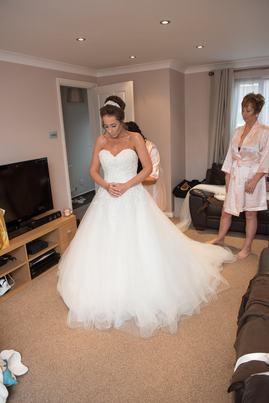 The finishing touches of the wedding dress being tied up