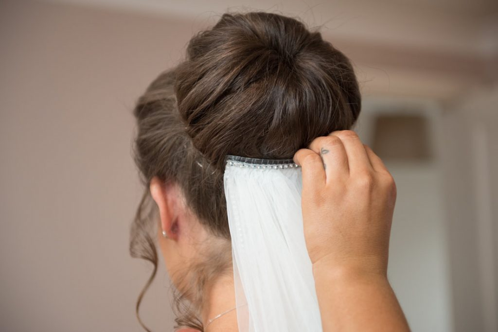 The wedding veil being fitted to the bride